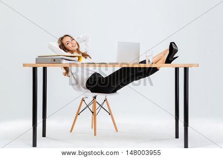 Relaxed young businesswoman sitting and relaxing with legs on table over white background