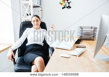Beautiful happy businesswoman relaxing at her workplace while sitting in office