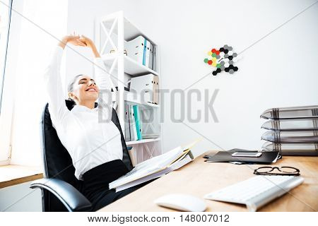 Beautiful smiling businesswoman stretching hands in office