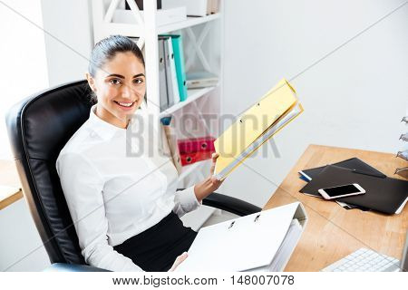 Happy beautiful businesswoman holding binders and looking at camera while sitting at the office