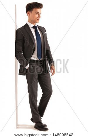 side view of a young business man leaning on white wall and looks away from the camera