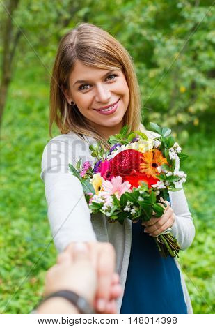 Portrait of a beautiful young woman holding a bouquet of flowers