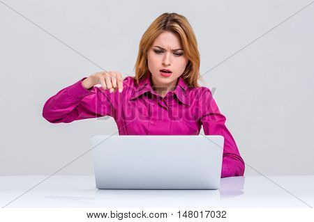 Young businesswoman working at laptop computer. she was surprised, prints and indignation is pointing at the monitor