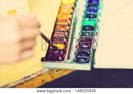 Paintbrush artist drawing watercolor picture dunks brush and painting