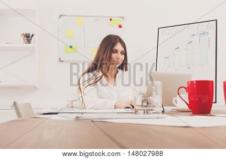 Beautiful young businesswoman sitting by wooden desk with laptop. Modern office worker in white room interior, red coffee cup on table. Succesfull woman, female carreer concept.