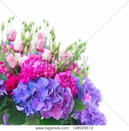 Bright pink peony, eustoma and blue hortensia flowers bouquet close up over white background