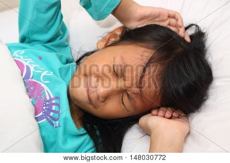 Little Asian girl having nightmare while sleeping