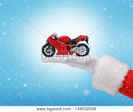 Hand in costume Santa Claus is holding red motorbike / studio shot of man's hand holding present / Merry Christmas & New Year's Eve concept / Closeup on blurred blue background.