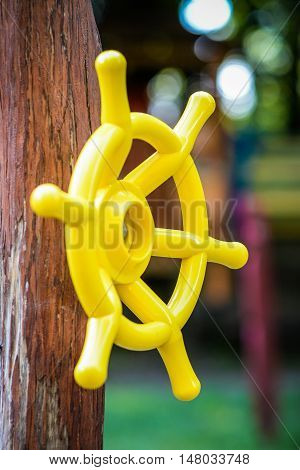 Yellow plastic children's handlebar of the ship a wooden girder on the playground