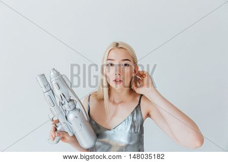 Close up portrait of a beautiful fashion blonde girl in silver shiny dress holding blaster isolated on the grey background