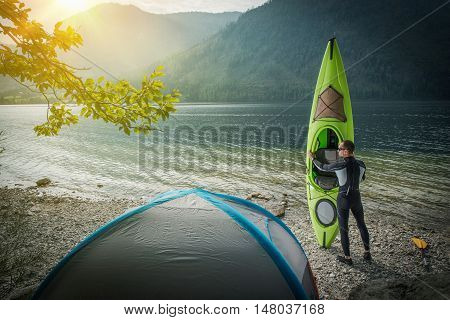 Kayak Tour Preparation. Caucasian Men with His Kayak and Lake Shore Located Tent Preparing For Kayak Tour. Kayaking Theme.