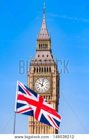Blurry Union Jack flag in front of London Big Ben clock tower and blue sky