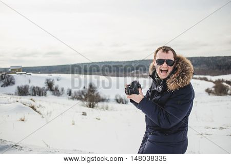 Hiker photographer enjoys a fine winter forest panorama at sunny day.