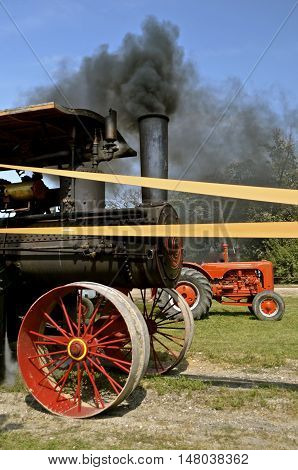 ROLLAG, MINNESOTA, Sept 1. 2016: A smoke blowing steam engine with an old Case tractor are displayed at the West Central Steam Threshers Reunion in Rollag, MN attended by 1000's held annually on Labor Day weekend.