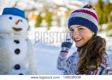 Happy smiling teenage girl playing with a snowman on a snowy winter village in mountains, Switzerland