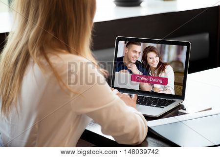 Young beautiful single woman browsing online dating website on a laptop display. Attractive woman model sitting with notebook searching for new love on-line. Close-up. Back view. Focus on screen