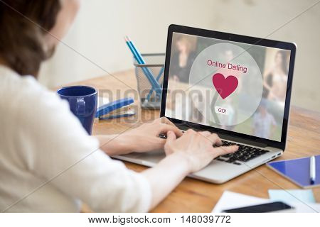 Young beautiful single woman browsing online dating website on a laptop display. Attractive woman model sitting with notebook searching for new love online. Back view over the shoulder