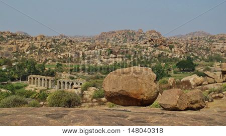 Unique landscape in Hampi India. Granite boulder and granite mountains. Ruined old bridge. Popular travel destination and place for rock climbing.