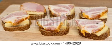sandwiches with cheese meat on a wooden board