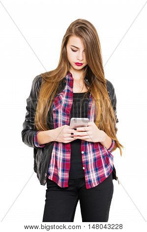 Millennial teenage girl with long blonde hair using smart phone texting. Cool young woman in red checkered shirt and black jacket and jeans, using mobile phone. Medium retouch, isolated on white.