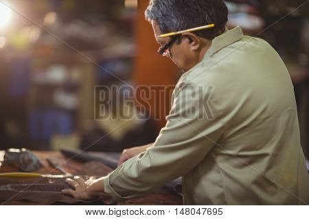 Shoemaker cutting a piece of leather in workshop