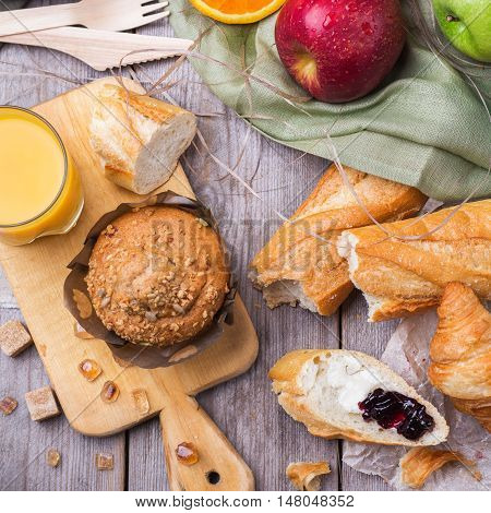 Still life, food and drink concept. Healthy muffin cake croissant french baguette for breakfast on a rustic wooden table. Selective focus, top view flat lay overhead