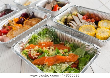 Healthy food delivery, daily ration. Take away low fat diet meals of vegetables, fruits, fish and meat. Fitness nutrition in foil boxes on white wood background. Proper protein and carb balance