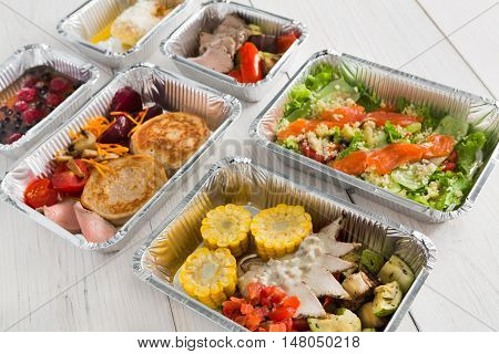 Healthy food delivery, daily ration. Take away low fat diet meals of vegetables, fruits, fish and meat. Fitness nutrition in foil boxes on white wood background. Proper protein and carb balance poster