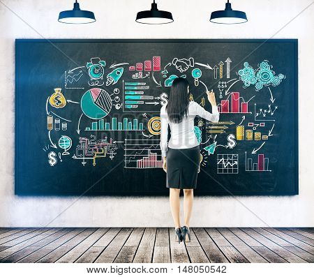 Rear view of business lady in black skirt drawing colorful startup sketch on blackboard in class. Concept of business planning. Toned image