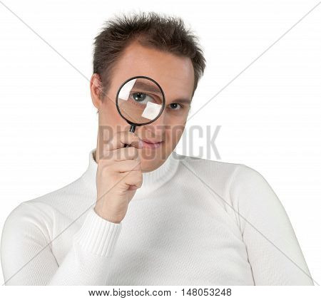 Young Man In White Sweater Looking At Camera Through Magnifying Glass Close-up - Isolated
