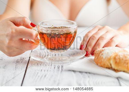 Woman in bra having breakfast in bedroom