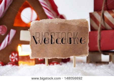 Gingerbread House In Snowy Scenery As Christmas Decoration. Sleigh With Christmas Gifts Or Presents. Label With English Text Welcome