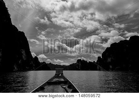 Black and white wooden boat with beautiful water sky and mountains in Ratchaprapha dam Surat Thani Thailand.