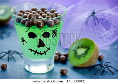Frankenstein kiwi jelly in glass with sweet chocolate balls for dessert. Funny idea for kids thematic party