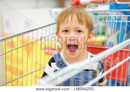 Boy sitting in a grocery cart and laughing funny face smile and curiosity indulge and makes faces. Boy rides in a cart at the mall at the grocery store