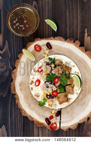 Mexican tacos with quinoa salad meat black beans and corn on rustic wooden table. Recipe for Cinco de Mayo party. Top view. Copy space background