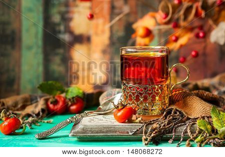 Glass of rose hip tea in a silver glass-holder and fresh berries