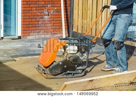 Vibratory plate compactor used to make the soil surface flat before paving the garden