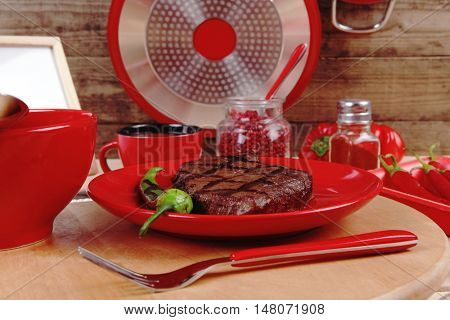 red theme lunch : grilled bbq roast beef steak red plate tomato soup sauce paprika jug glass ground pepper american peppercorn modern cutlery served wooden plate over table empty nameplate menu board