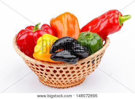 varicoloured bell peppers in basket on white background