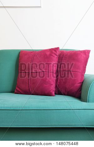Green sofa and red backrest pillow in living room