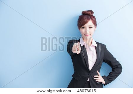 business woman is smile and pointing to you isolated on blue background asian