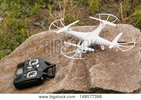 White quadrocopter on stone with remote control, close-up. New unmanned aerial copter. Electronics innovation. Modern Technologies. Aeromodelling