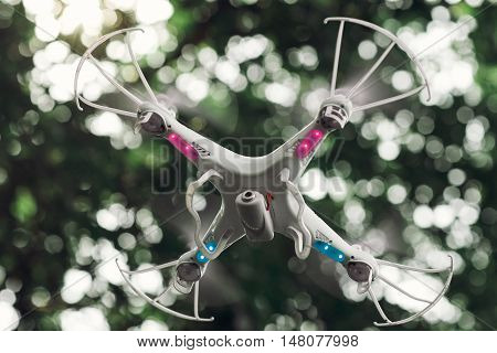Quadrocopter while flying in the forest. Unmanned aerial copter flight. Aeromodelling, hobby, modern technologies