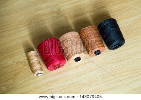 Many Colored Sewing Threads Of Leather Crafting On Wood Table.