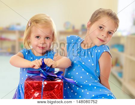 Two charming little girls , sisters, in identical blue dresses with polka dots. Girl looking at gifts Packed in beautiful red paper tied with a bow.On the background of the room where children live