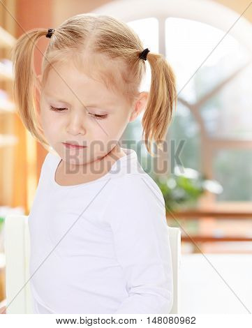 The concept of pre-school education of the child among their peers . in gaming room with a large arched window.Distressed small, blonde girl with white t-shirts without a pattern.