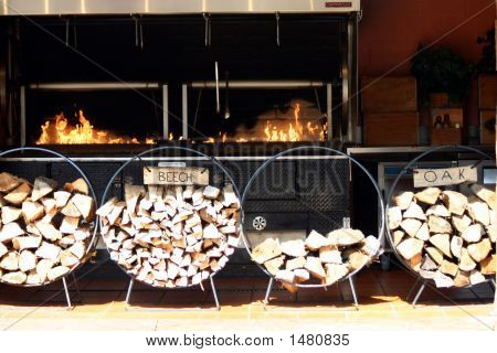 Stacks Of Wood In Rack With Fire Behind