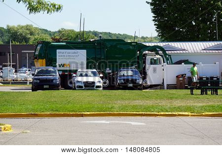 HARBOR SPRINGS, MICHIGAN / UNITED STATES - AUGUST 1, 2016: A Waste Management garbage truck empties a dumpster at the Harbor Master's office in Harbor Springs.