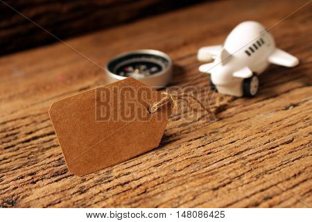 paper tag or label with pastic airplane toy and compass on woodenconcept idea for travelbusiness
